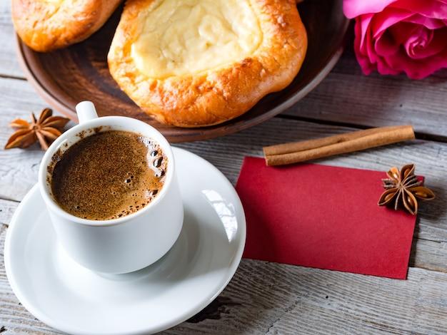 Ouvrez les petits pains avec du fromage cottage (vatrushka) dans une assiette en argile sur une table en bois avec carton rose et rouge.
