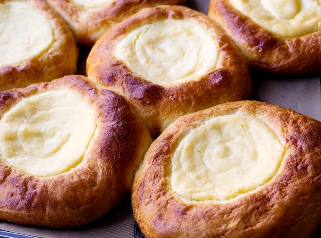 Ouvrez les petits pains avec du fromage cottage (vatrushka) se trouvant sur un plateau après la cuisson. fermer