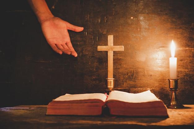 Ouvrez la sainte bible et bougie sur une vieille table en bois de chêne.