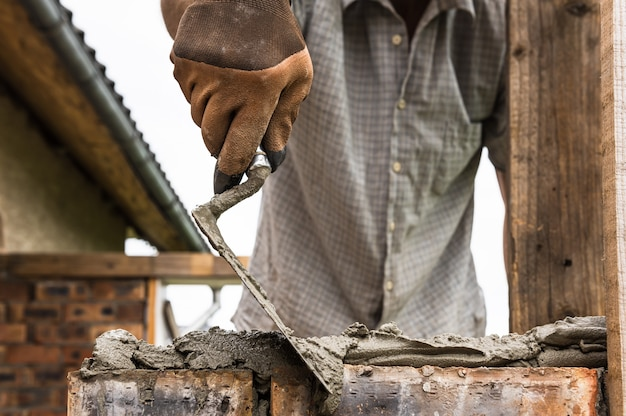 Un ouvrier applique un mortier avec une truelle sur la brique.