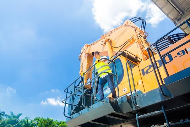 Ouvrier asiatique, sur, pelle, chantier construction