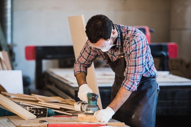 Ouvrier broie le bois de la machine de meulage angulaire