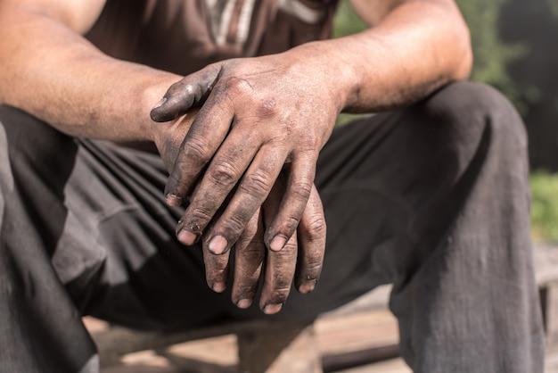 Ouvrier brûleur de charbon de bois avec les mains sales. ouvrier, mains