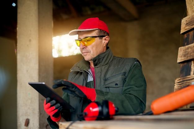 Ouvrier charpentier moderne tenant une tablette dans l'atelier.