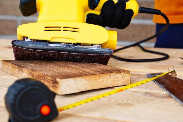 Ouvrier charpentier travaillant avec le ponçage du bois et enlevant la couche supérieure avec une ponceuse.