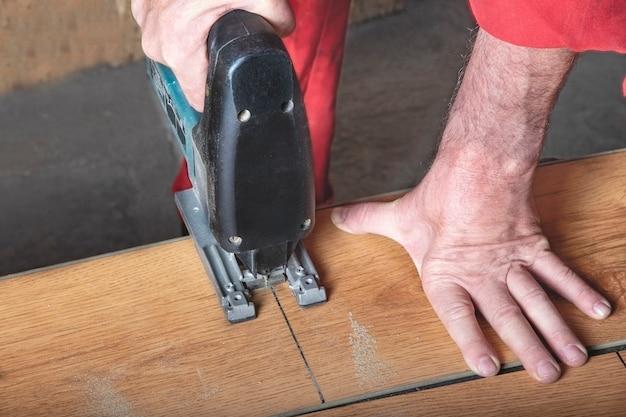 Un ouvrier en combinaison rouge coupe un stratifié avec une scie sauteuse en marquant le sien au repos dans l'atelier