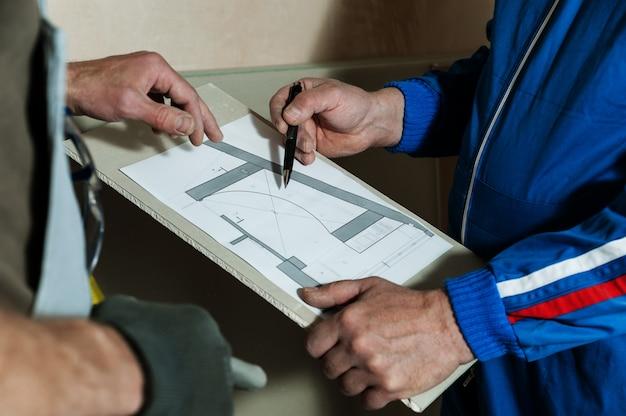 Un ouvrier et un contremaître discutent du schéma du plafond en plaques de plâtre