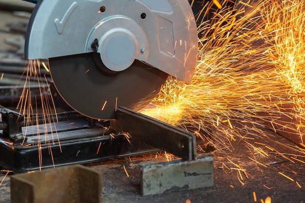 Ouvrier coupant du métal avec une meuleuse. des étincelles lors du meulage