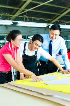 Ouvrier, couturier et pdg dans une usine