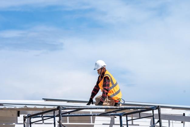 Ouvrier couvreur portant des uniformes de protection et des gants travaillant à l'installation de tôles sur le nouveau toit sur le chantier de construction.