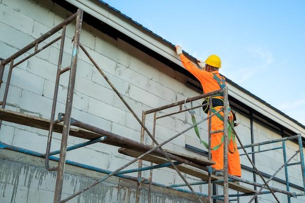 Ouvrier couvreur en uniforme de protection contre l'usure et la ligne de sécurité travaillant installer un nouveau toit sur le chantier de construction.