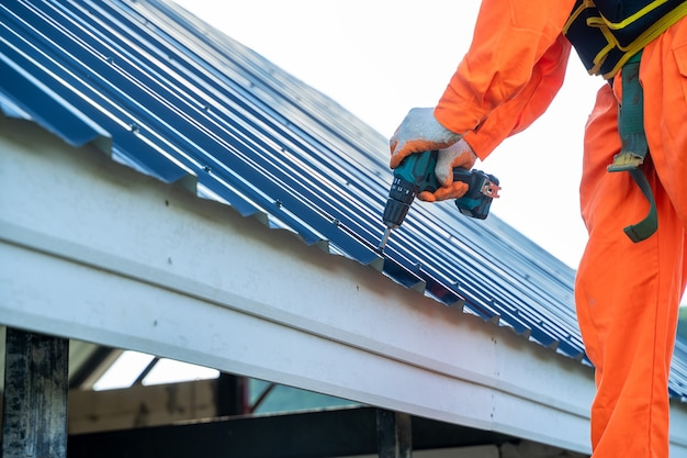 Ouvrier couvreur en uniforme de protection portant l'installation d'un nouveau toit