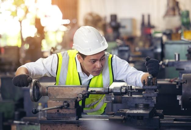 Un ouvrier dans des verres debout près de l'équipement industriel et vérifie la production. homme d'exploitation de la machine dans l'usine