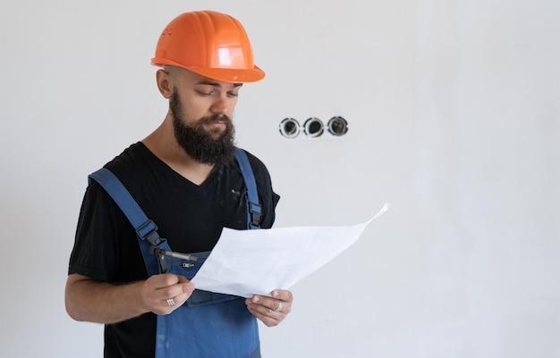 Ouvrier du bâtiment brutal dans des vêtements de travail spéciaux et un casque orange. tenez le dessin en main. feuille de papier froissée. espace libre
