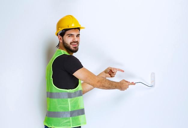 Ouvrier du bâtiment avec un casque jaune peignant le mur blanc avec un rouleau de finition.