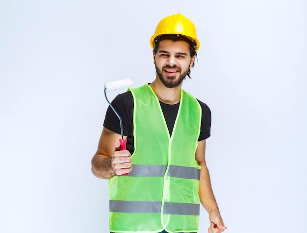 Ouvrier du bâtiment avec un casque jaune tenant un rouleau de finition blanc.