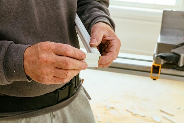 Ouvrier du bâtiment, coupe de parquet à l'aide d'une scie circulaire à onglet