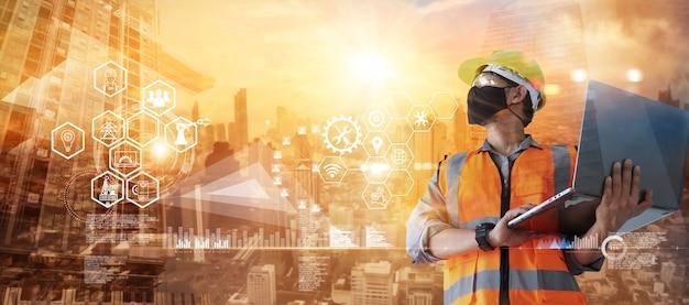 Ouvrier du bâtiment à double exposition avec masque et ordinateur portable en main avec construction d'icônes