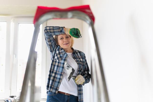 Ouvrier du bâtiment féminin avec un outil de construction