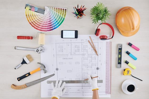 Ouvrier du bâtiment mesure plan de maison