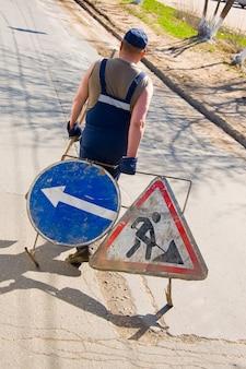 Un ouvrier du bâtiment porte des panneaux routiers