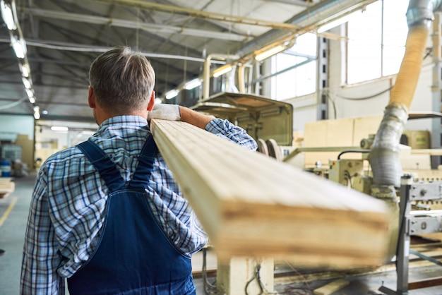 Ouvrier du bâtiment transportant des planches