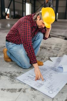 Ouvrier du bâtiment vérifiant les empreintes et parlant au téléphone