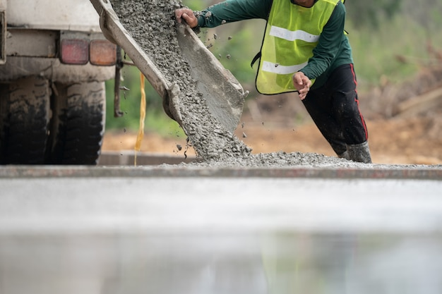 Un ouvrier du bâtiment verser un béton humide sur le chantier de construction de la route