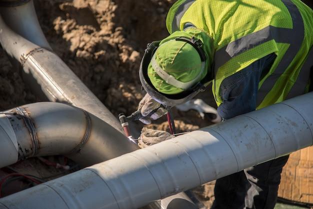 Ouvrier du bâtiment de vue de dessus soudant le tuyau en acier dans le chantier de construction souterrain
