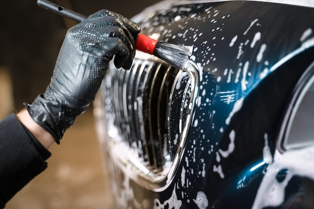 Un ouvrier du centre de nettoyage nettoie la calandre de la voiture avec une brosse