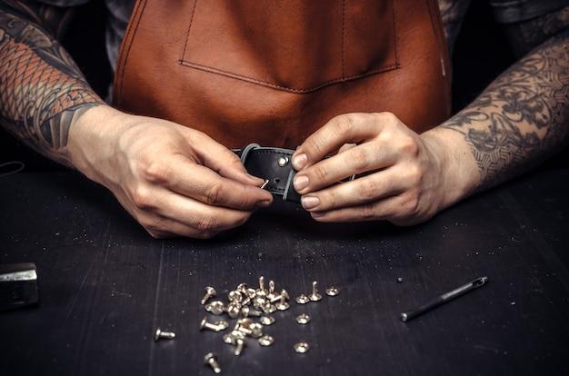 Ouvrier du cuir découpant les contours du cuir pour sa nouvelle production dans son atelier.