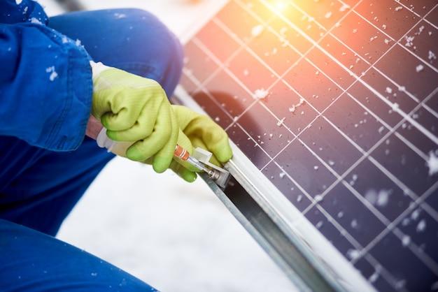 Ouvrier électricien professionnel installant des panneaux solaires