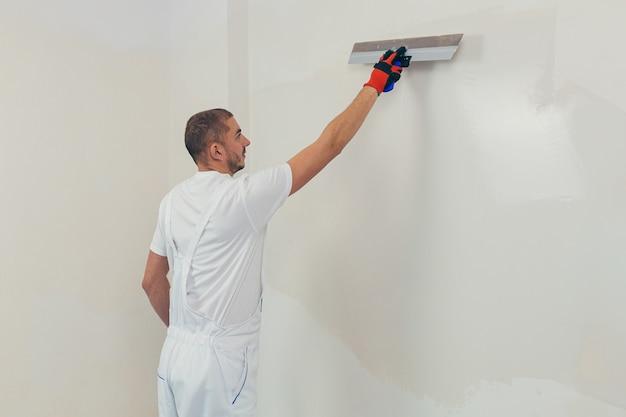 Un ouvrier enduit les murs d'une maison nouvellement construite
