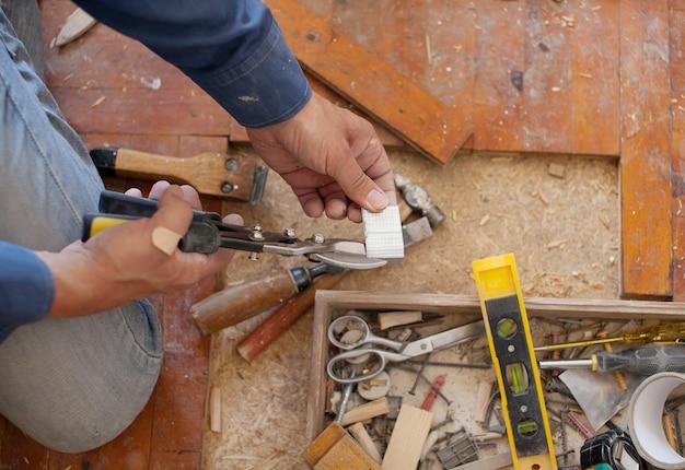 Ouvrier Enlevant L'ancien Plancher. Vue Rapprochée De Ses Mains Gantées Photo Premium