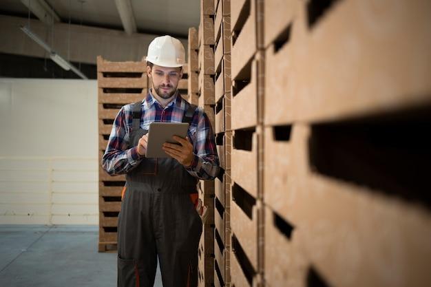 Ouvrier d'entrepôt du caucase vérifier l'inventaire des marchandises sur ordinateur tablette dans la salle de stockage de l'usine.