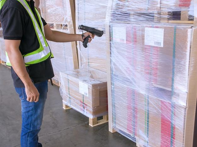 Ouvrier d'entrepôt tient un lecteur de code à barres avec balayage sur la palette d'expédition du produit