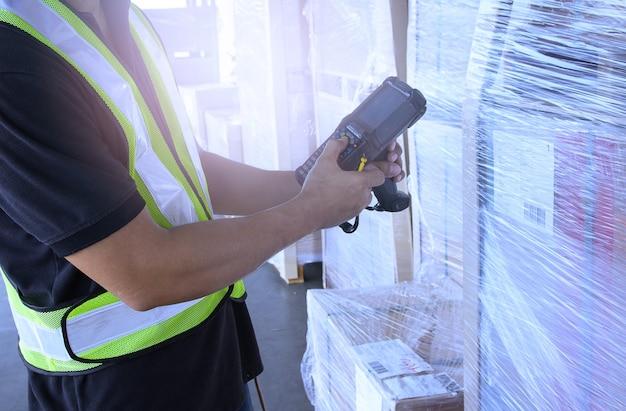 Ouvrier d'entrepôt tient un lecteur de code à barres avec inventaire et vérifie les produits