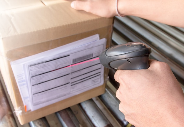 Ouvrier d'entrepôt tient un lecteur de code à barres avec numérisation sur le produit.