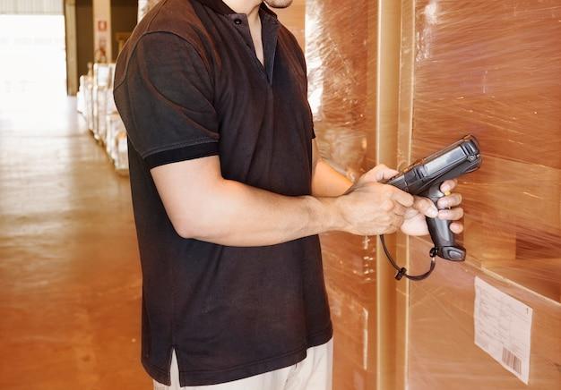 Ouvrier d'entrepôt tient un lecteur de codes à barres avec inventaire des produits en entrepôt.