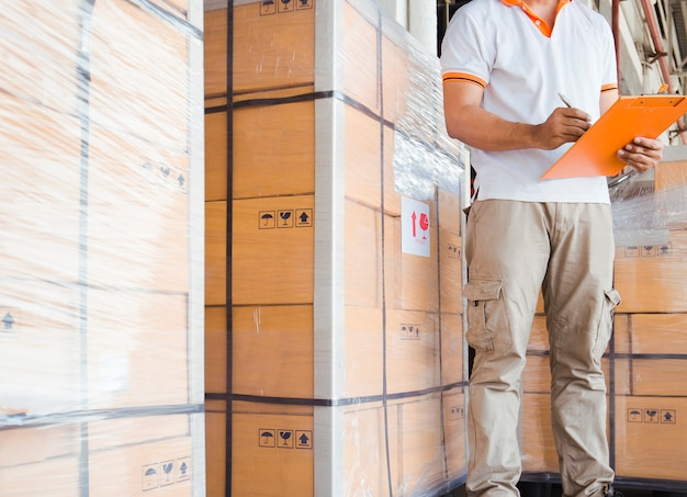 Ouvrier d'entrepôt tient un presse-papiers écrit sur la fiche technique avec l'inventaire des produits