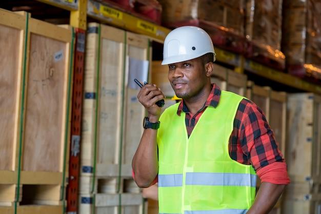 Ouvrier d'entrepôt utilisant un récepteur radio portable pour la communication dans un grand entrepôt.