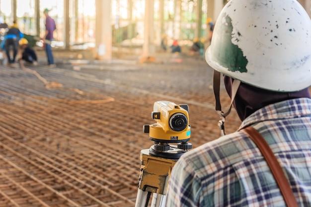 Un ouvrier géomètre effectue des mesures avec un équipement au théodolite sur le site de construction de l'usine.