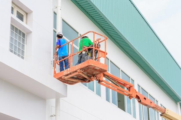 Ouvrier, homme, sur, a, ciseaux hydraulique, table élévatrice, plate-forme, vers, a, toit usine, à, constructi