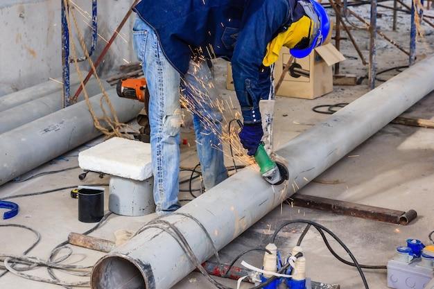 Ouvrier de l'industrie lourde coupant un tuyau d'acier avec un masque de protection contre l'usure par une scie mécanique