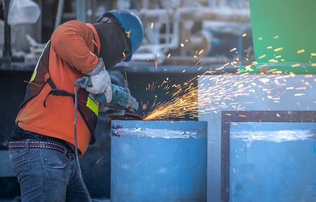 Ouvrier industriel coupant et soudant du métal avec de nombreuses étincelles pointues
