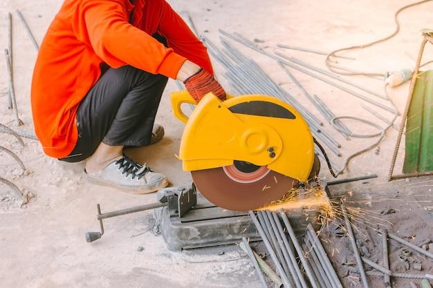 Ouvrier industriel coupant des tiges de renforcement en métal avec beaucoup d'étincelles tranchantes