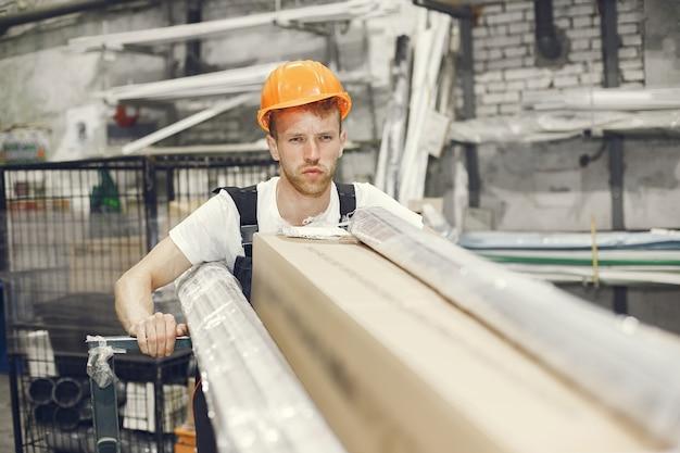 Ouvrier industriel à l'intérieur en usine. jeune technicien avec casque orange.