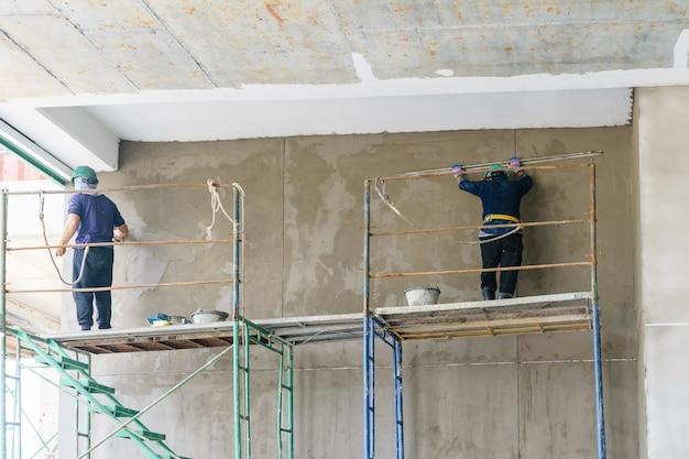 Ouvrier industriel avec des outils de plâtrage rénovant une maison