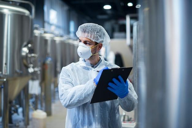 Ouvrier industriel portant un masque de protection et des vêtements blancs tenant une liste de contrôle en usine.