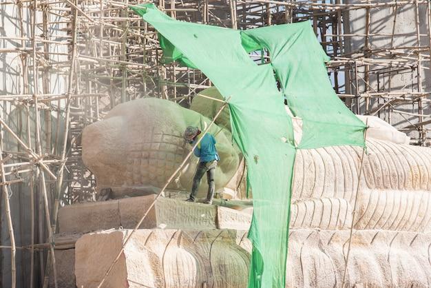 Ouvrier industriel utilisant une meuleuse d'angle professionnelle pour tailler la pierre de bouddha.